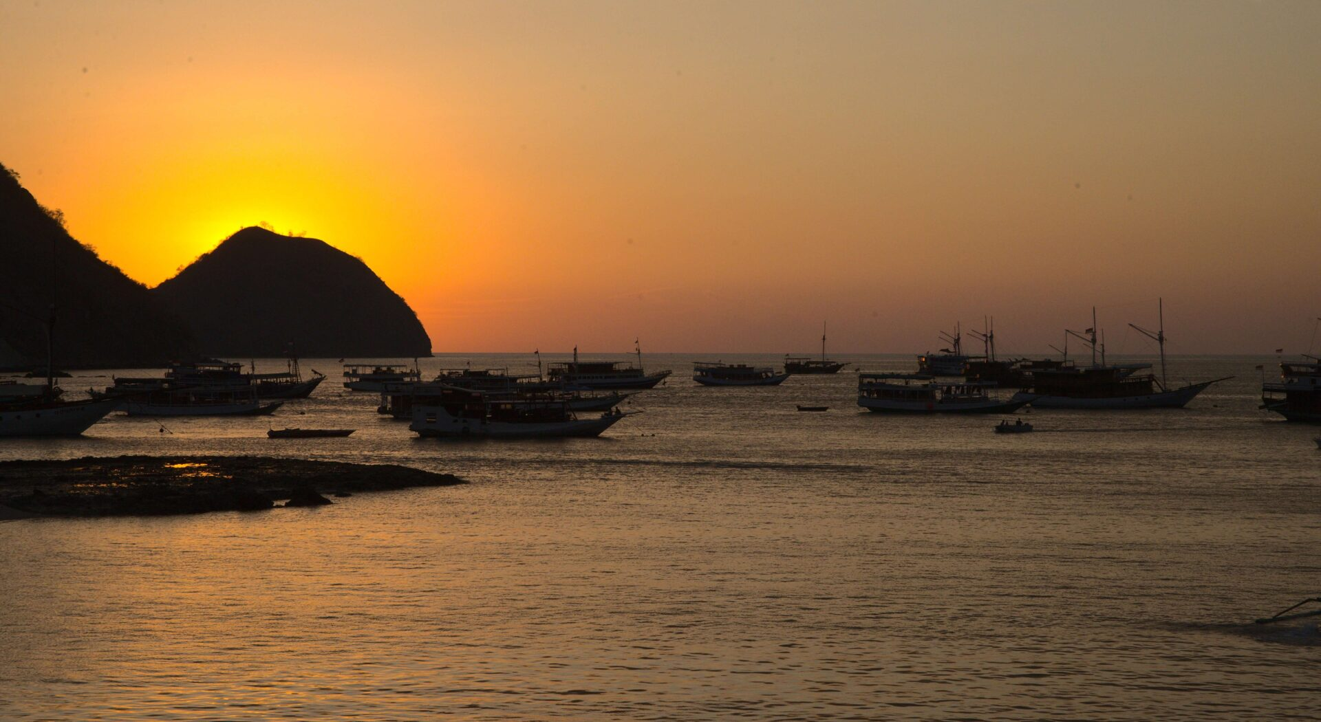 Det gule sitrondropset stiger ned i vest over båtmetropolen Labuan Bajo. Fotoꓽ Amanda Sailing